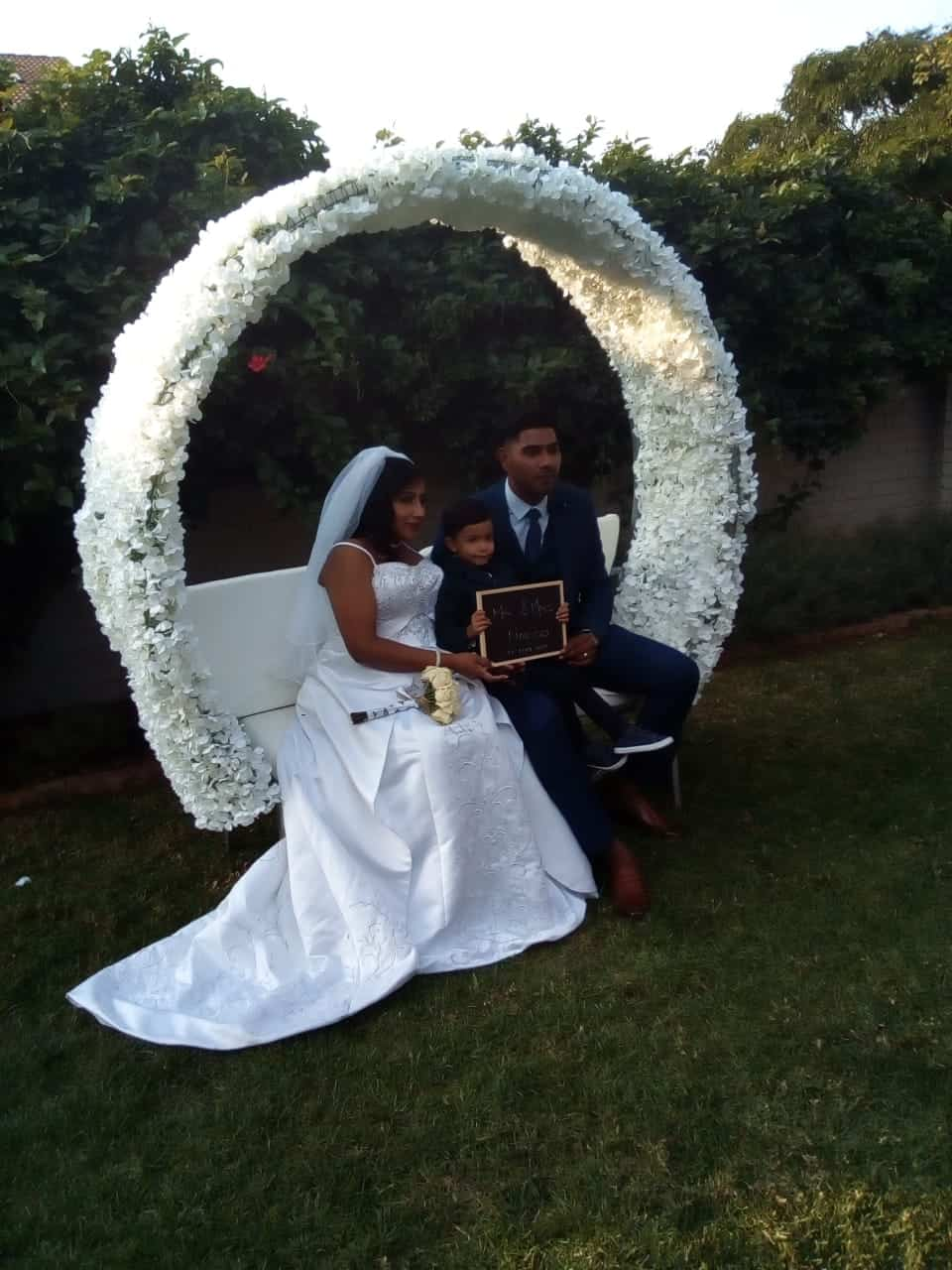 Bride and groom sittign on a flower arch