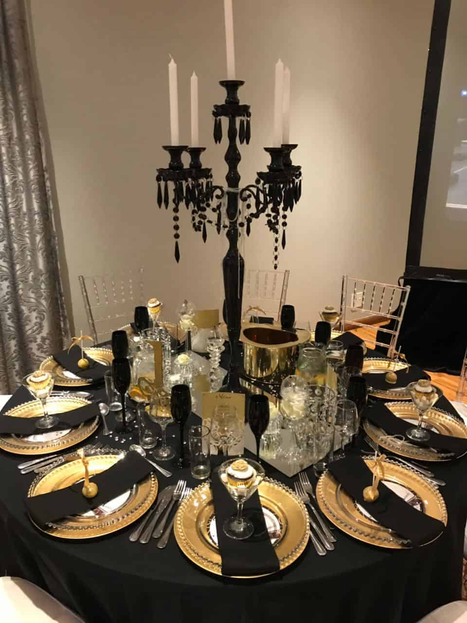 Gold Plates on black overlay with candle centrepiece