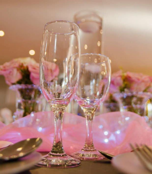 champagne glasses on table with pink accents