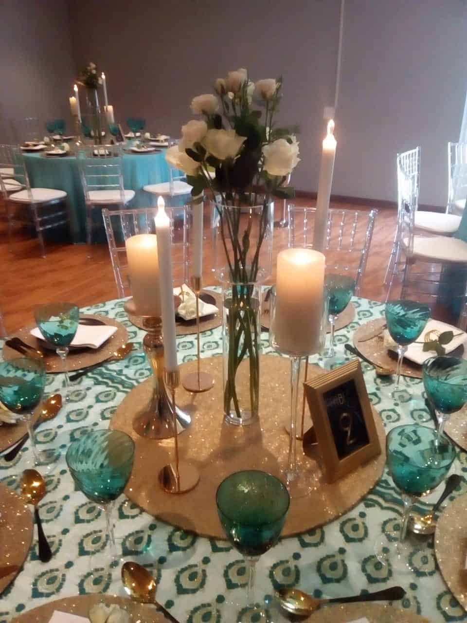 green and turquoise place setting on a table with candles