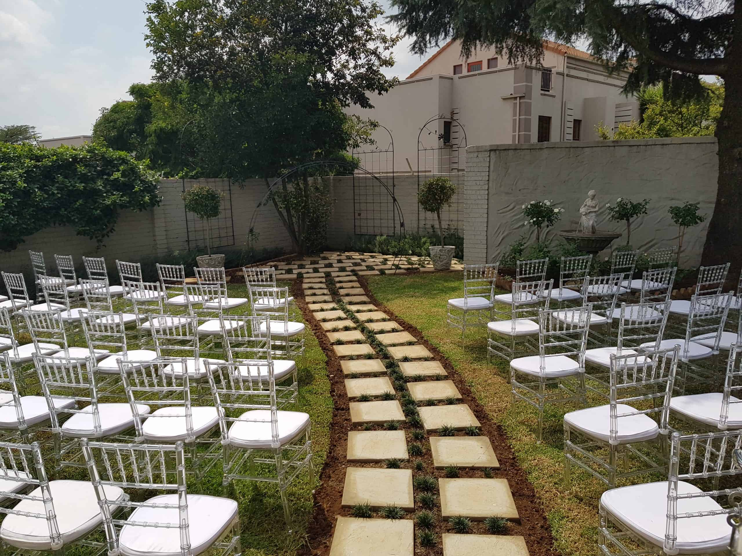 outdoor wedding with path leading to the wedding arch scaled