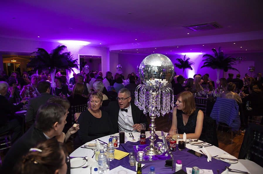 purple lights with people around a round table with mirror ball