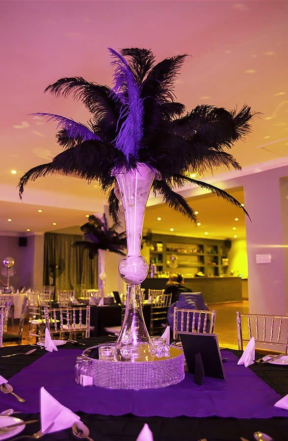 purple table setting with mirrors and feathers with table number