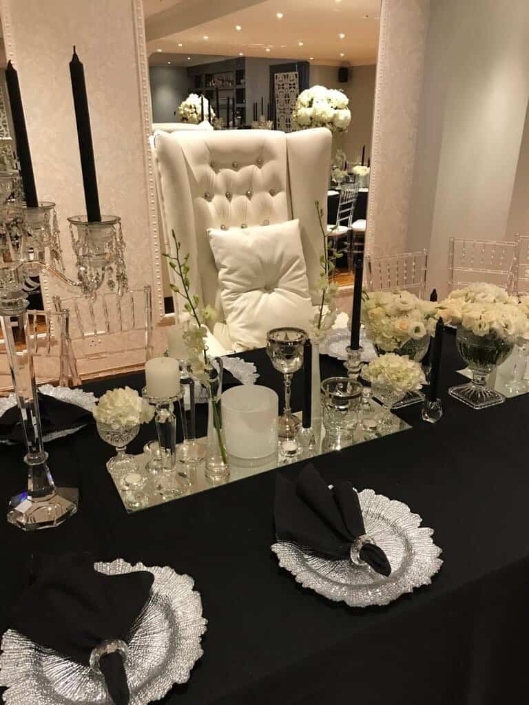 white chair with black table covering and beautiful flowers